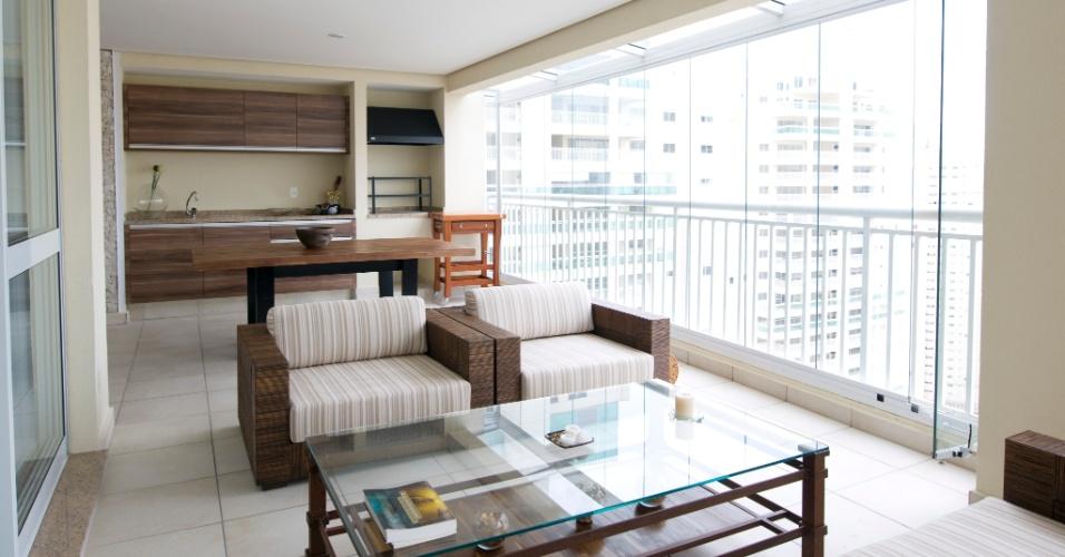 Na varanda gourmet assinada pela arquiteta Heloisa Dabus, os móveis de madeira da Segatto dão o tom ao ambiente. O armário acima da bancada amplia o espaço para os itens de cozinha e, à direita, sobrou espaço para a instalação de uma churrasqueira