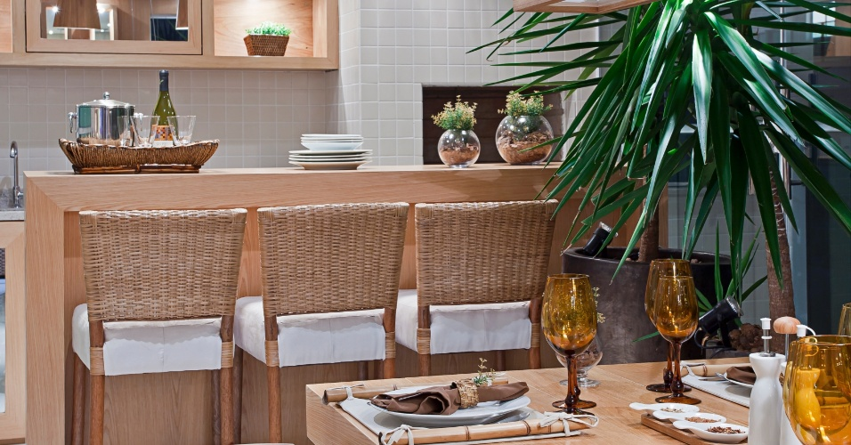 Na varanda gourmet com predominância da madeira nos móveis, a arquiteta Maithiá Guedes deu espaço ao verde, posicionando próximo ao balcão, uma planta de médio porte que se destaca na decoração