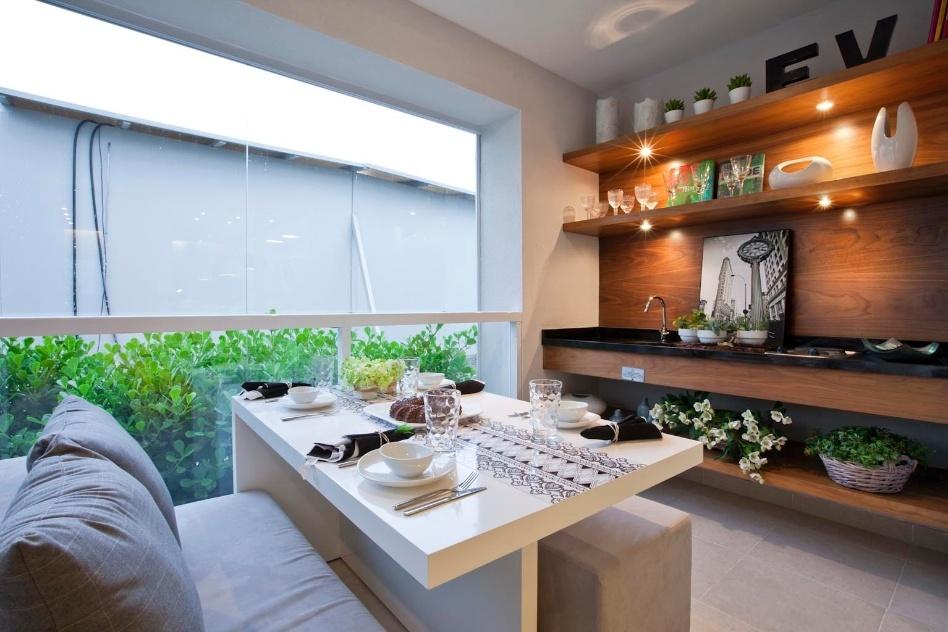 Na varanda gourmet desenhada pela arquiteta Fernanda Marques, as cadeiras foram substituídas por dois pufes e um sofá de dois lugares. As prateleiras, unidas à bancada por meio da painel de madeira, foram ocupadas por vasos com flores e objetos de decoração