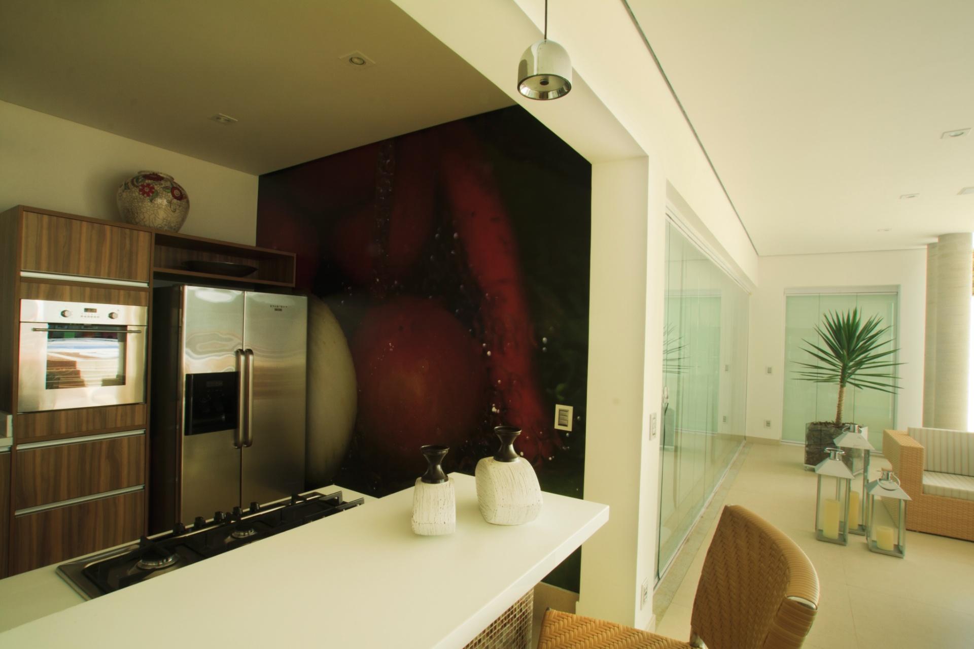 No detalhe da ampla varanda gourmet, desenhada pela arquiteta Cristiane Schiavoni, a cozinha com cooktop, refrigerador e forno embutido oferece boa base para a preparação de refeições completas