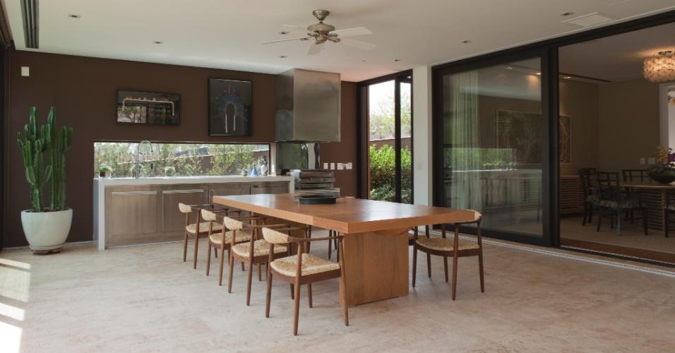 No projeto da varanda gourmet, a arquiteta Clarissa Strauss eliminou parte da parede acima da bancada 9ao fundo), substituindo-a por vidro. Com a mudança, é possível visualizar o jardim externo da residência
