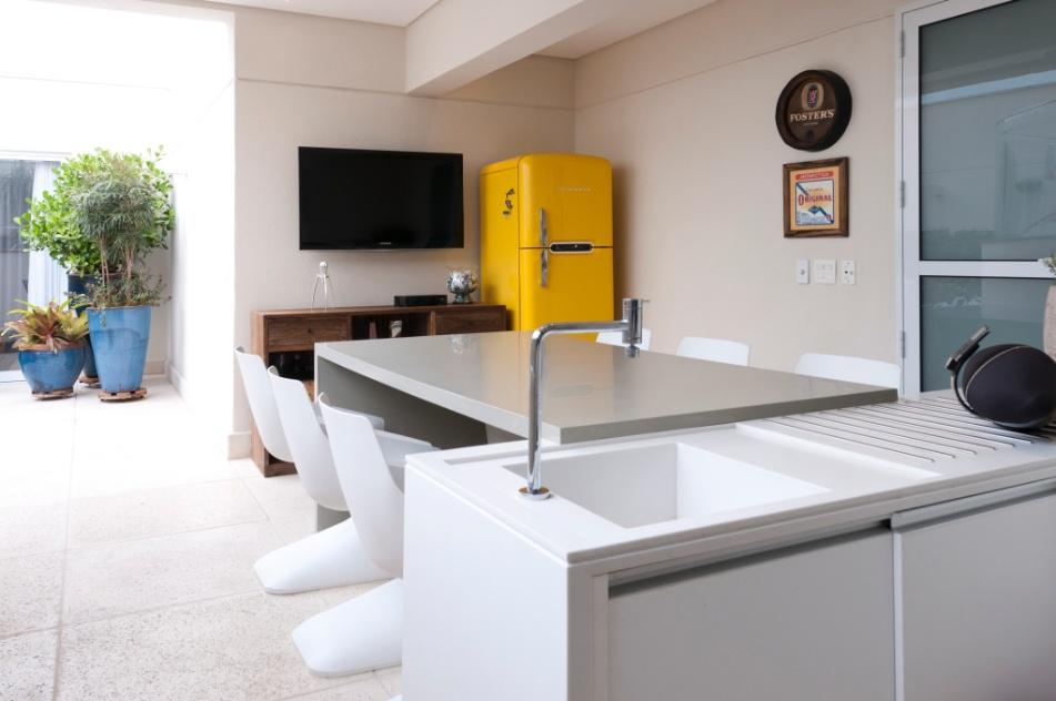 """Para aproveitar melhor o espaço disponível, os arquitetos Olegário Sá e Gilberto Cioni escolheram para varanda gourmet uma mesa retangular junto à bancada. Destaque para a geladeira na cor amarela e desenho """"vintage"""""""