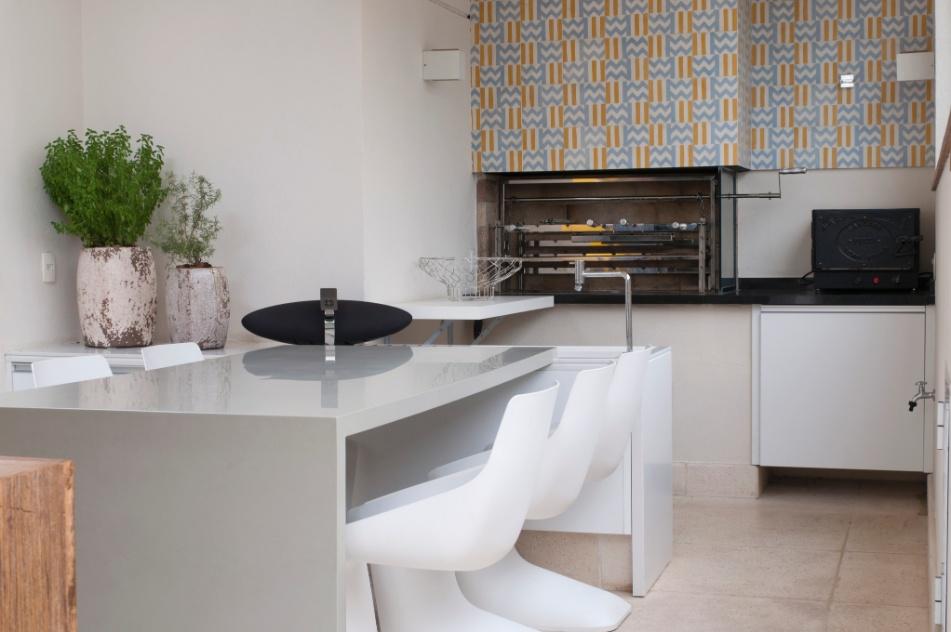 Para aproveitar melhor o espaço disponível, os arquitetos Gilberto Cioni e Olegário Sá escolheram para varanda gourmet uma mesa retangular junto à bancada. O acabamento da parede acima da churrasqueira, nas cores amarelo e azul, dá um ar retrô ao ambiente