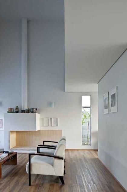 A janela lateral garante a entrada de luz natural no ambiente de estar que tem lareira com desenho criativo e revestimento de tijolos na parte interna. A Casa do Moinho foi projetada pela arquiteta Nora de Queiroz
