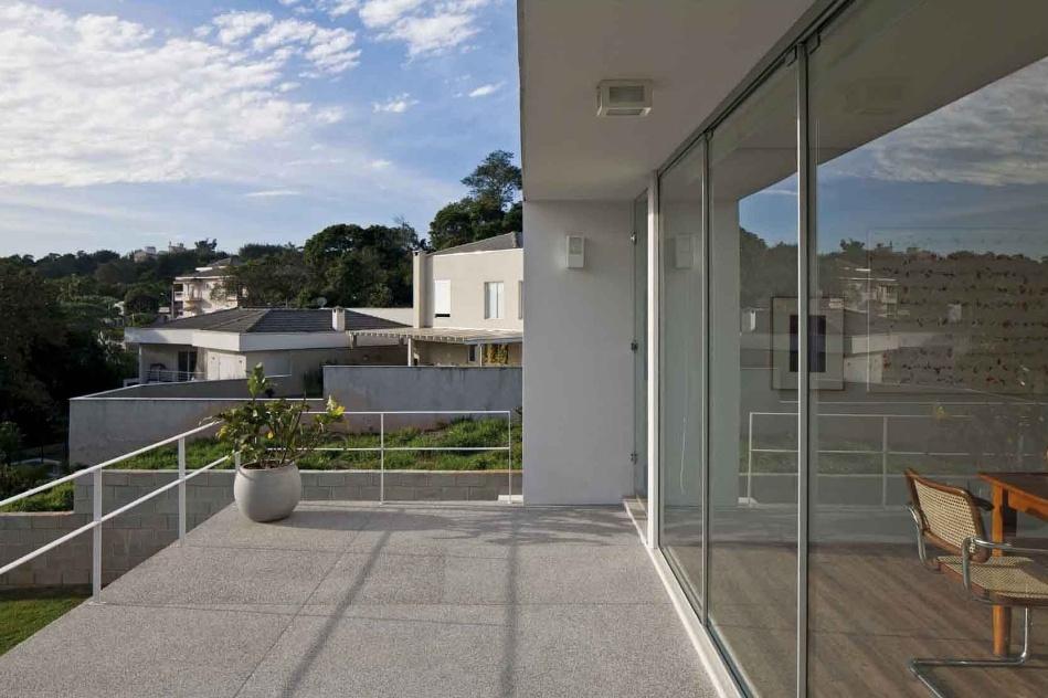 Portas de correr de vidro temperado, da Temperal, com esquadrias de alumínio - da Alumicorte - separam e interligam num só tempo a sala de jantar e o terraço com piso fulget, da Arco Íris Quartzo. A Casa do Moinho tem projeto da arquiteta Nora Queiroz
