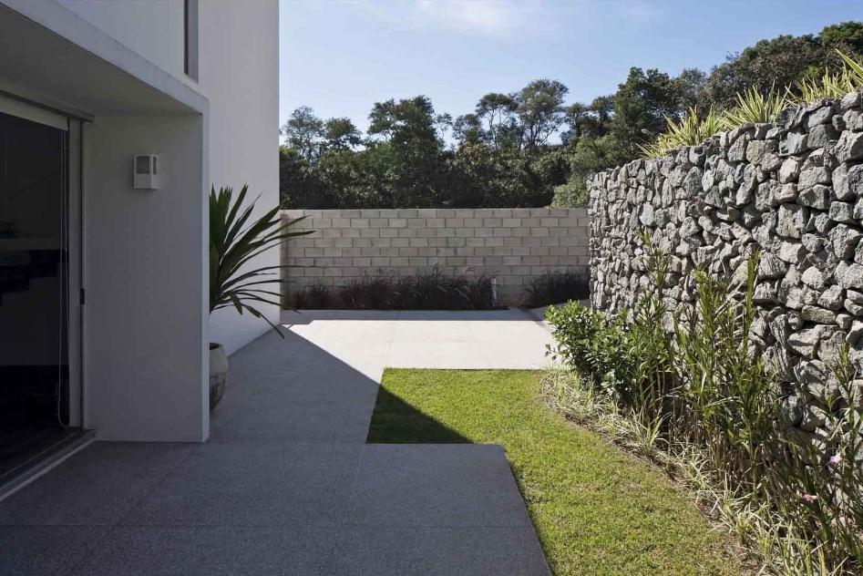 O muro de blocos de concreto faz a divisa com a lateral nordeste da Casa do Moinho, projetada por Nora de Queiroz, enquanto o muro de pedras rachão delimita o espaço privado em relação à rua. O terraço da residência tem piso fulget