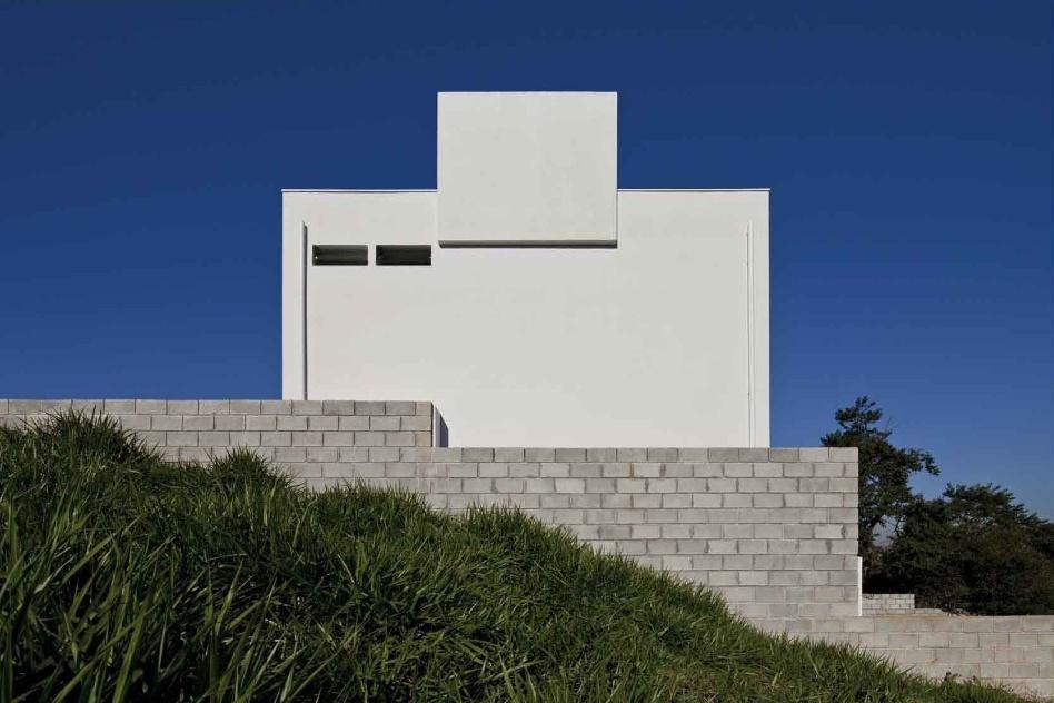 O volume da caixa d'água tem uma de suas faces ligeiramente deslocada em relação ao plano da fachada nordeste. Em primeiro plano, o muro de blocos de concreto protege e isola a residência. O projeto da Casa do Moinho é da arquiteta Nora Queiroz