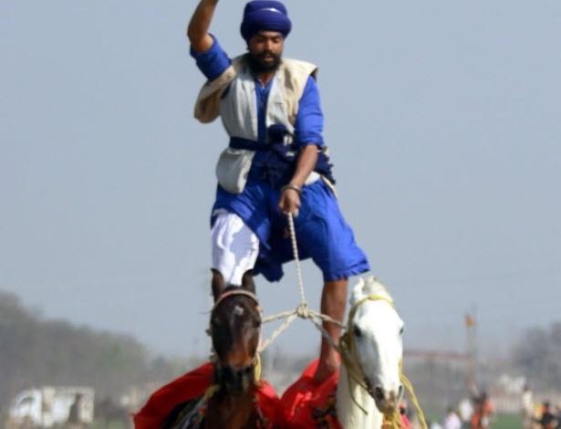 02.fev.2013 - Homem fica em pé sobre dois cavalos, com uma perna em cada, durante prova das Olimpíadas Rurais da Índia, que reúne esportes tradicionais do local