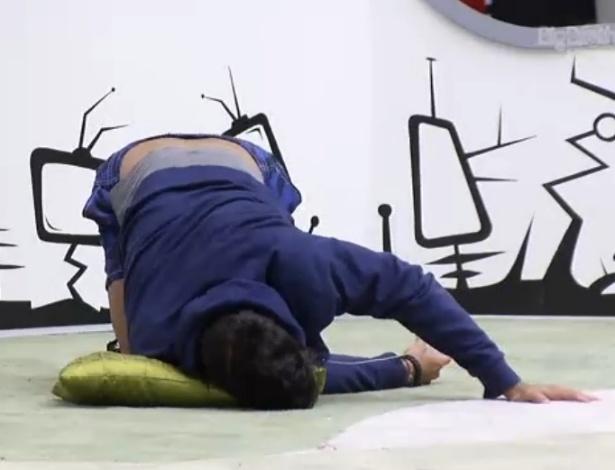2.fev.2013 - O personal Marcello faz alongamento com a ajuda de uma almofada no chão da sala