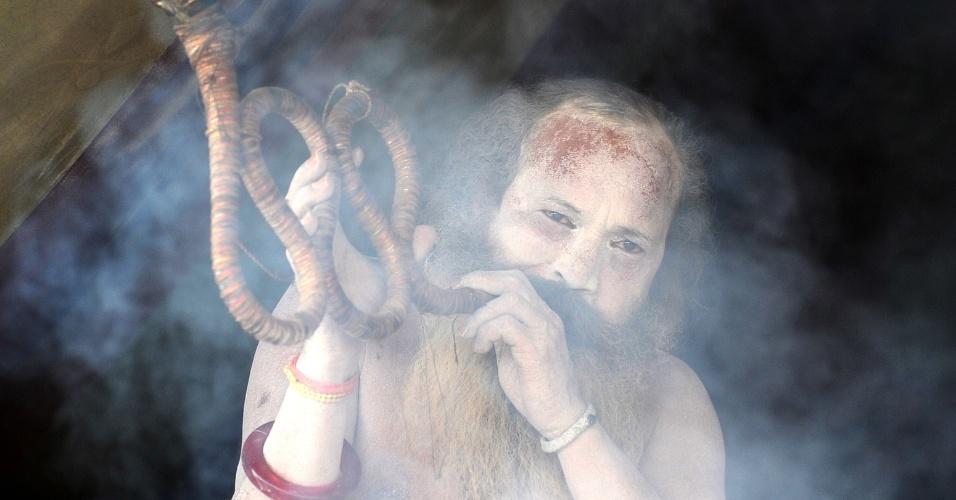 3.fev.2013 - Religioso hindu toca instrumento musical com formato de cobra durante o festival Maha Kumbh, neste domingo (3), em Allahabad (Índia). Cerca de 100 mil peregrinos devem participar do evento, que dura 55 dias