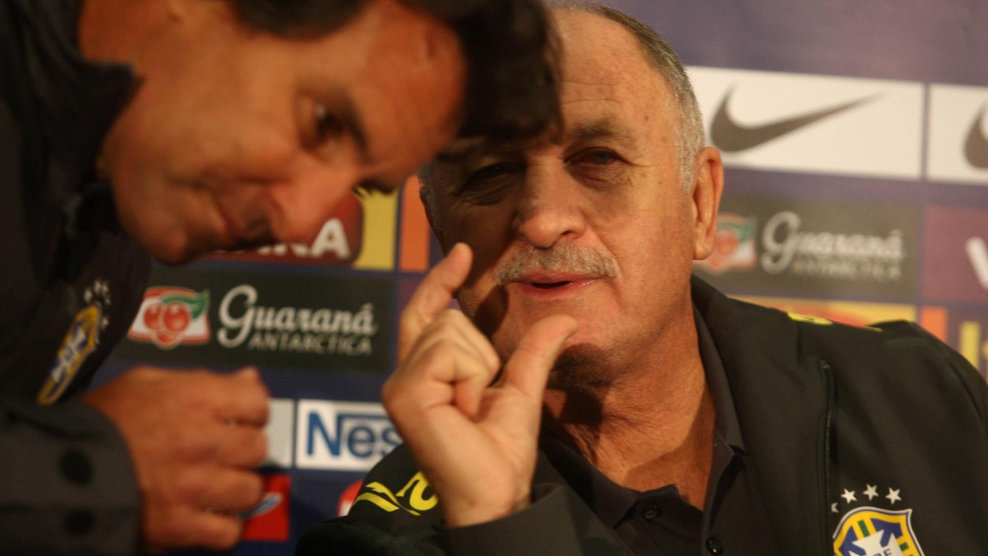 05.fev.2013 - Scolari conversa com Rodrigo Paiva, assessor da CBF, durante coletiva em Londres, antes do amistoso da seleção com a Inglaterra