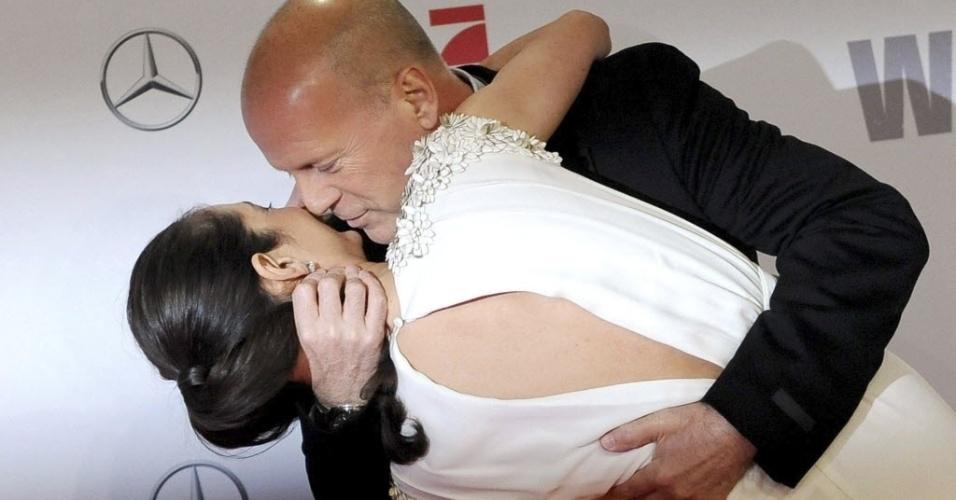 4.fev.2013 - Bruce Willis dá beijo apaixonado na sua mulher, Emma Heming-Willis, na pré-estreia de