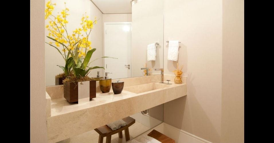 Flores no banheiro tornam o ambiente mais colorido e elegante. A orquídea amarela escolhida é da espécie conhecida como chuva de ouro ou oncídio; disposta em cachepô de madeira, trouxe vida à bancada de mármore crema marfil do projeto da arquiteta Cristiane Schiavoni