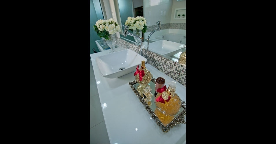 Vidros de perfumes organizados em uma bandeja espelhada enriquecem a decoração deste banheiro projetado pelo arquiteto Leonardo Dias