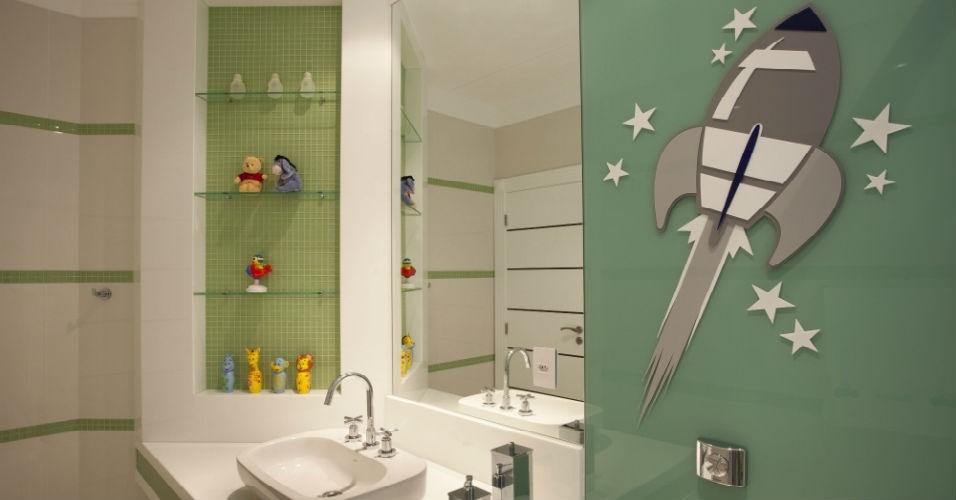 Um banheiro comum pode se tornar o lugar preferido das crianças, basta garantir que objetos de banho divertidos sejam dispostos nas prateleiras. O foguete foi feito de acrílico e colado a um painel de vidro, neste projeto do arquiteto Aquiles Nícolas Kílaris