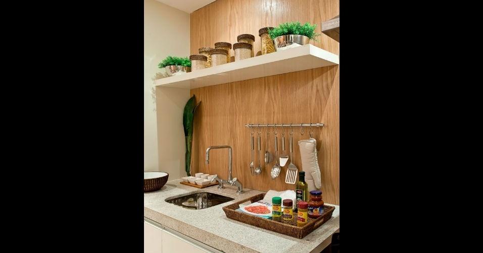 O charme pode estar apenas nos objetos. Nesta cozinha, a arquiteta Maithiá Guedes expôs potes de mantimentos e bandejas organizadoras com detalhes de rattan