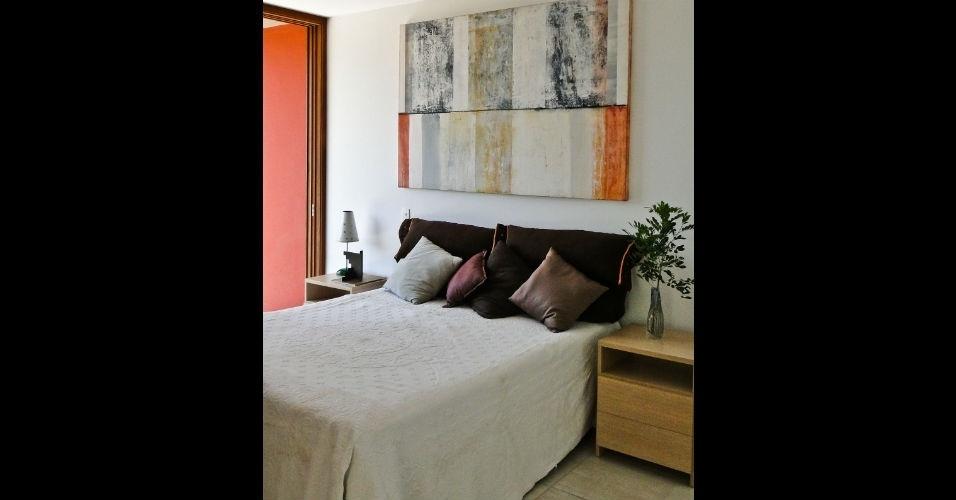 O quadro posto sobre a cabeceira da cama levou colorido ao quarto e harmonizou com a porta do cômodo e as almofadas. O projeto é do arquiteto Flavio Castro