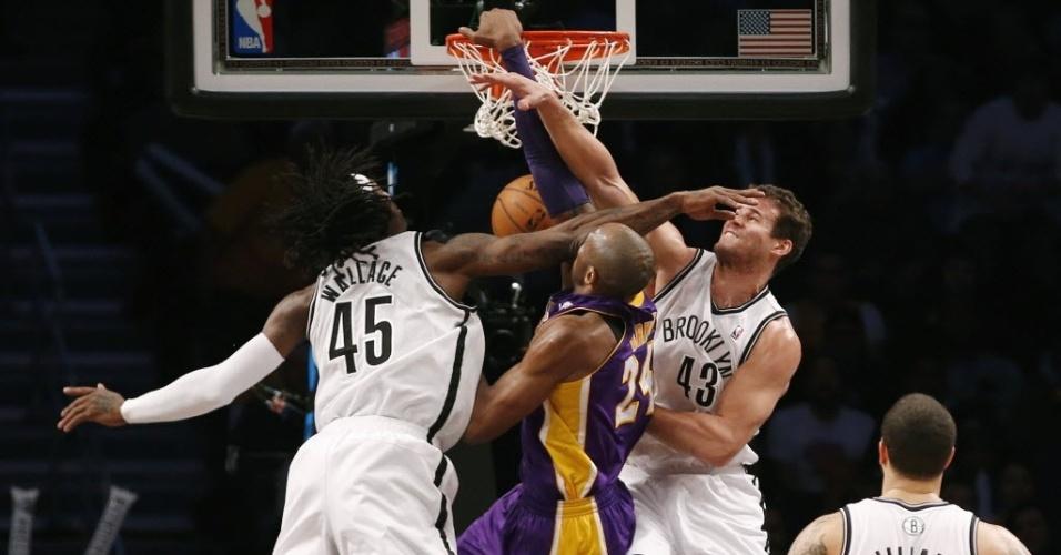 05.fev.2013 - Kobe Bryant dá belíssima enterrada entre Kris Humphries e Gerald Wallace, na vitória dos Lakers sobre os Nets