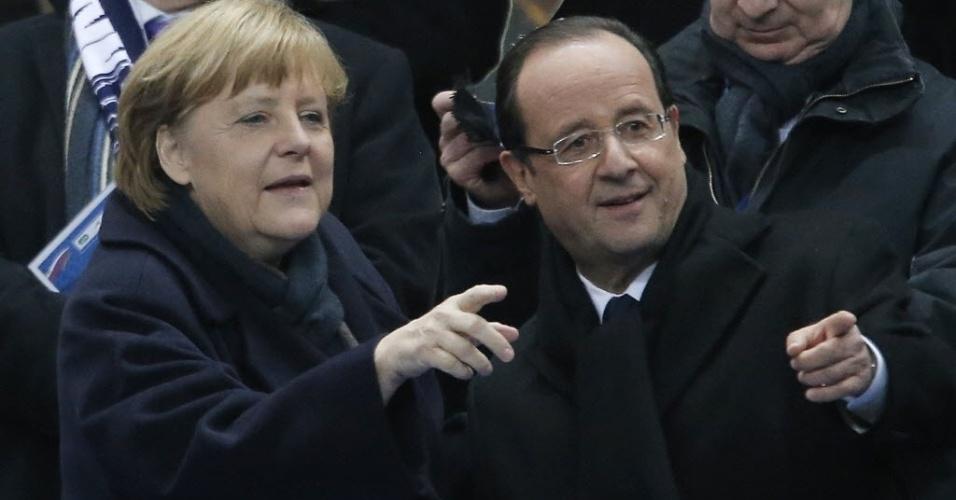 06.fev.2013 - Francois Hollande (dir.), presidente da França, e Angela Merkel, Chanceler da Alemnha, assistem ao jogo entre as duas seleções em partida amistosa