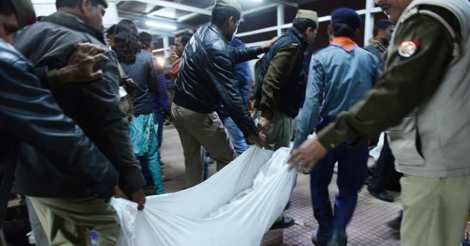 Autoridades indianas removem o corpo de uma das vítimas na confusão que ocorreu na estação de trem em Allahabad, neste domingo (10)
