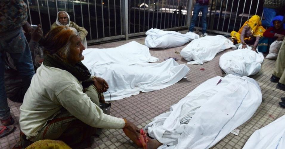 Mulher acaricia pé de seu parente morto durante um tumulto na estação de trem de Allahabad, na Índia. Ao menos dez pessoas morreram no momento em que peregrinos voltavam das celebrações no festival Kumbh Mela