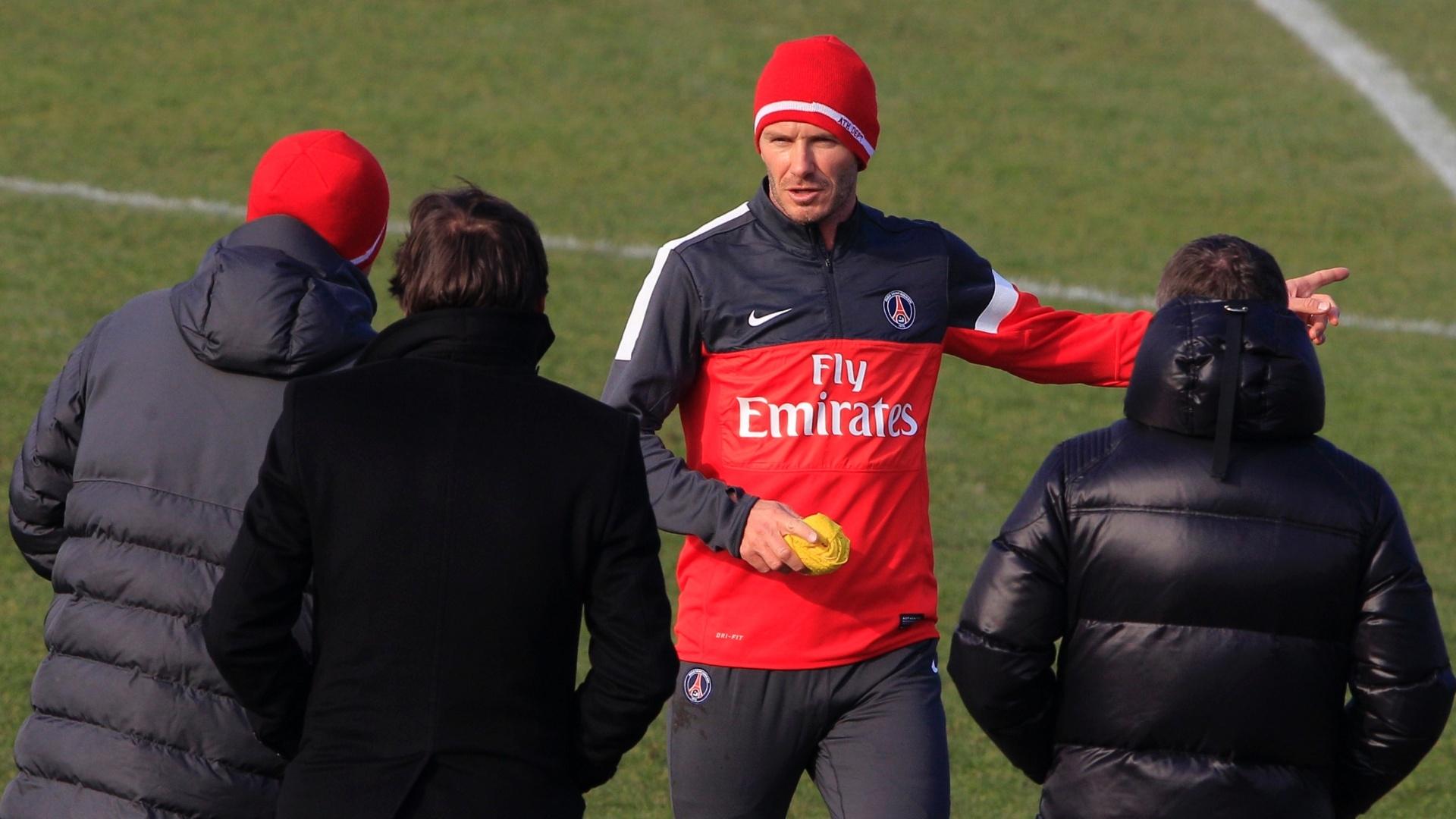 13.fev.13 - David Beckham conversa com o diretor do PSG, Leonardo, e com o técnico Carlo Ancelotti (ambos de costas) durante seu primeiro treino no clube francês