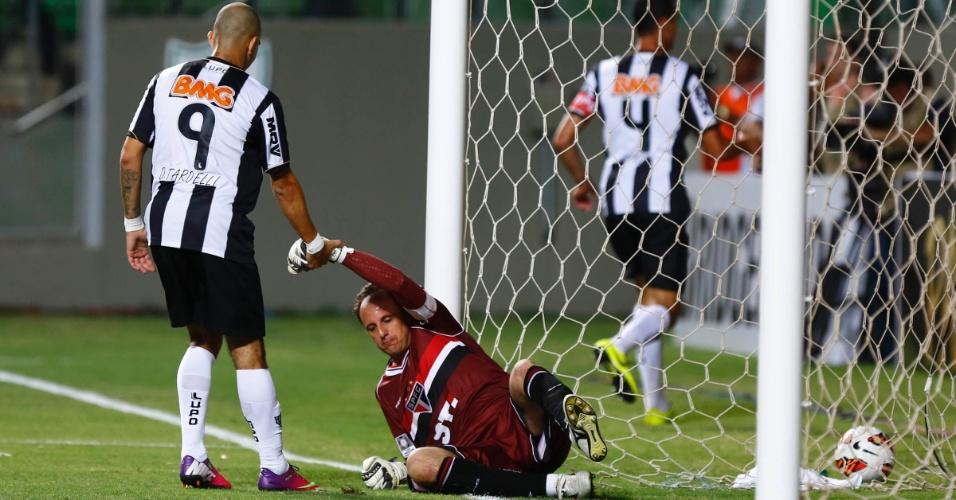 13.fev.2013 - Diego Tardelli, do Atlético-MG, ajuda Rogério Ceni, do São Paulo, a se levantar