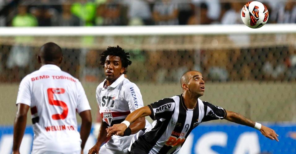 13.fev.2013 - Diego Tardelli, do Atlético-MG, observa a bola enquanto é observado por Cortez e Wellington, do São Paulo