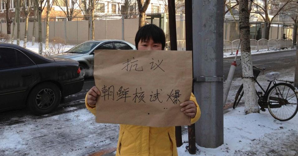 """13.fev.2013 - Manifestante mostra cartaz onde se lê: """"protesto contra a realização do teste nuclear da Coreia do Norte"""", em frente ao consulado norte-coreano em Shenyang, na província chinesa de Liaoning"""