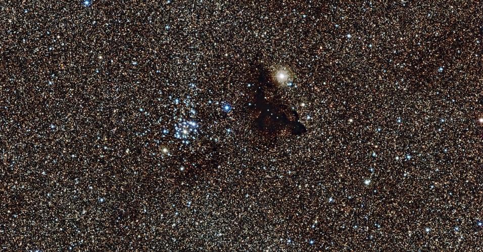 """13.fev.2013 - O brilhante aglomerado estelar NGC 6520 tem como 'vizinha cósmica' a nuvem escura Barnard 86, que possui o estranho formato de uma lagartixa. Essa nuvem densa e fria é composta por pequenos grãos de poeira que bloqueiam a radiação estelar, fazendo com que a região pareça opaca e """"crie"""" um buraco na região estrelada. O aglomerado, que tem cerca de 150 milhões de anos, está a uma distância de 6.000 anos-luz e abriga estrelas jovens e azuis"""