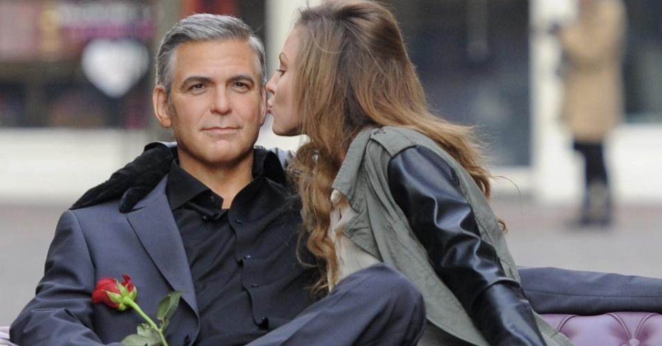 """13.fev.2013 - O Carnaval passou e você percebeu que ficar sozinho só é legal nos dias de folia? Corra para a Carnaby street, em Londres, no Reino Unido, onde um """"George Clooney"""" está à sua espera com uma rosa na mão, sentado em uma poltrona bem confortável. O boneco de cera, pertencente ao museu britânico Madame Tussauds, arranca quase tantos suspiros quanto o original e foi colocado no meio da rua em homenagem ao Valentine's Day (Dia de São Valentim), o dia dos namorados comemorado em vários países no..."""