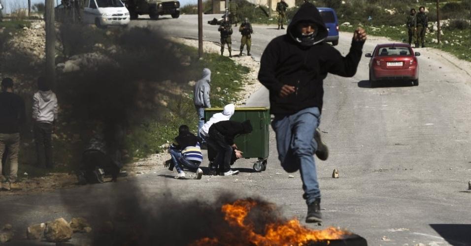 13.fev.2013 - Palestino corre para se proteger de tiros de borracha disparados pela polícia durante manifestação em apoio aos prisioneiros palestinos em Israel, perto do posto de controle de Atara, na Cisjordânia