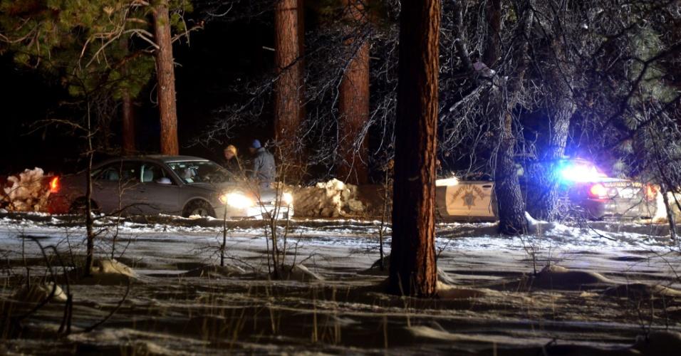 13.fev.2013 - Policiais revistam carro em estrada perto de Angeles Oaks, no Estado americano da Califórnia, durante buscas pelo ex-policial Christopher Dorner, acusado do assassinato de três pessoas, em 2008