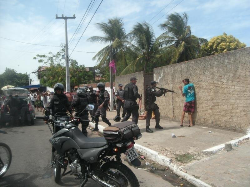 """13.fev.2013 - Policiais são flagrados abordando foliões com metralhadoras na praia da Redinha, em Natal (RN), durante durante o desfile do bloco """"Baiacu na Vara"""", nesta Quarta-Feira de Cinzas (13)"""
