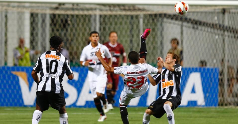 13.fev.2013 - Douglas, do São Paulo, tenta afastar a bola enquanto recebe a marcação de Bernard, do Atlético-MG
