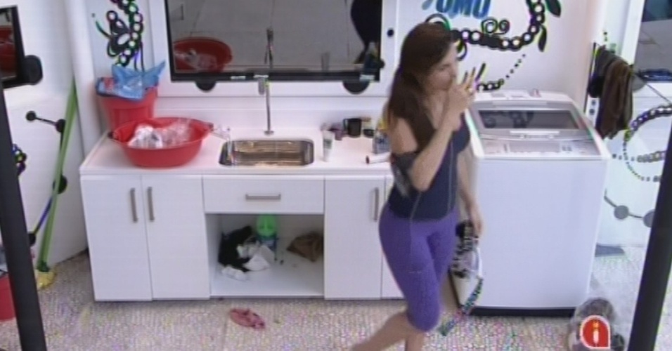 14.fev.2013 - Kamilla busca roupas que havia deixado para lavar