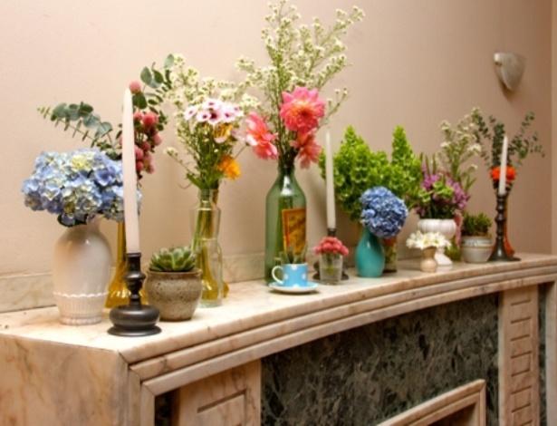 Flores colocadas em antigas garrafas, xícaras e vasos dão ar romântico, rústico e vintage à decoração do casamento