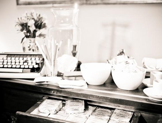 Mesa decorada com uma máquina de escrever e jogo de chá
