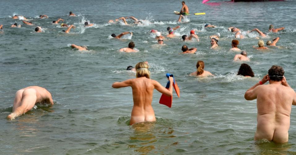 17.fev.2013 - Homens e mulheres entram nus no mar para nadar, em Sydney (Australia), neste domingo (17). Eles participam de evento que incentiva as pessoas a tentarem algo diferente e estimula que se jogue fora as preocupações com a imagem corporal