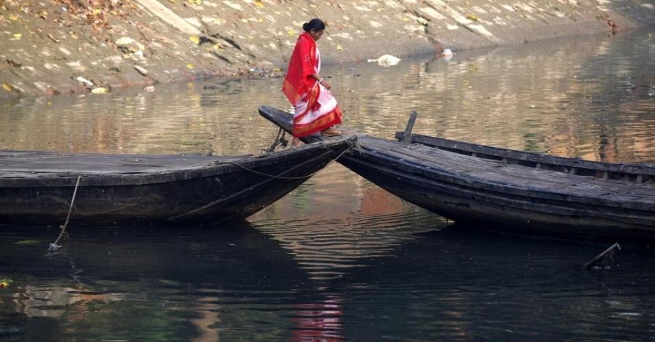 19.fev.2013 - Mulher anda sobre dois barcos, usados como ponte para atravessar canal em Kolkata (Índia)