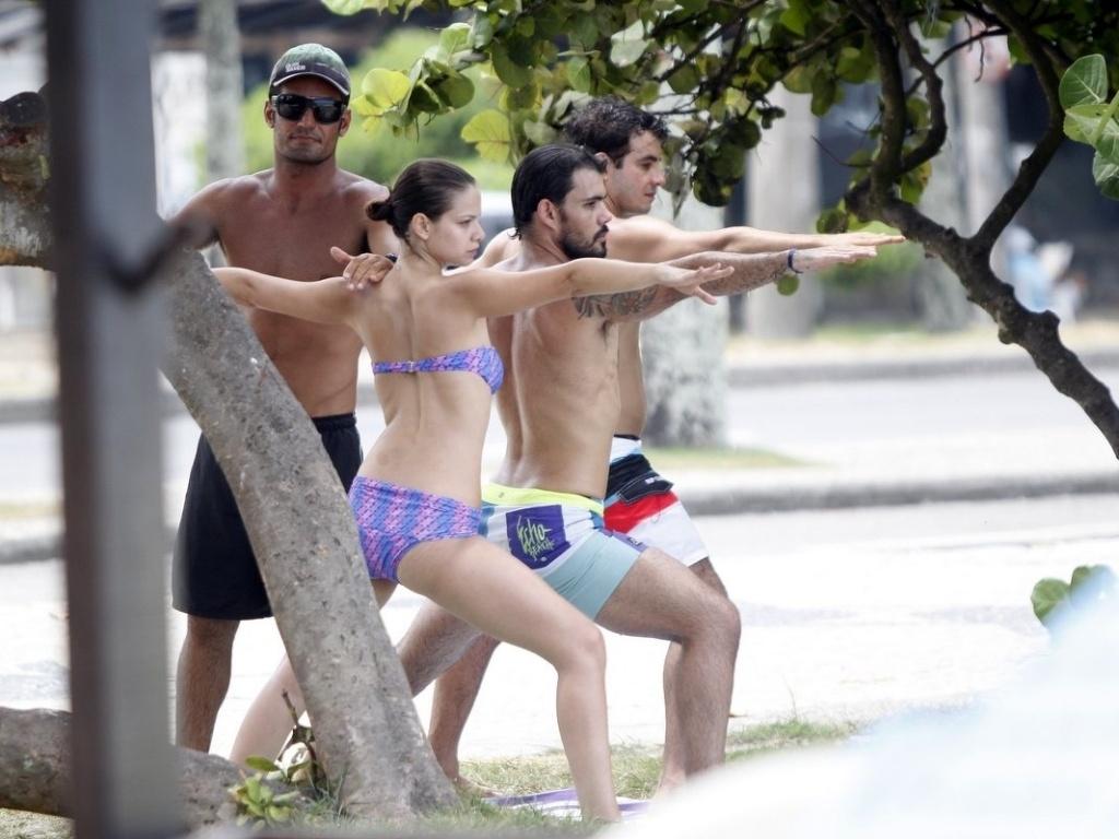 19.fev.2013 - Os atores Milena Toscano e Juliano Cazarré fazem aquecimento antes de entrarem no mar para praticar stand-up paddle
