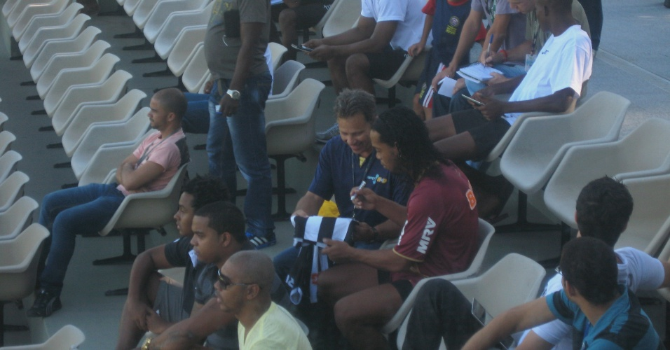 20 fev 2013 - Ronaldinho Gaúcho autografa camisa de torcedor atleticano na Cidade do Galo