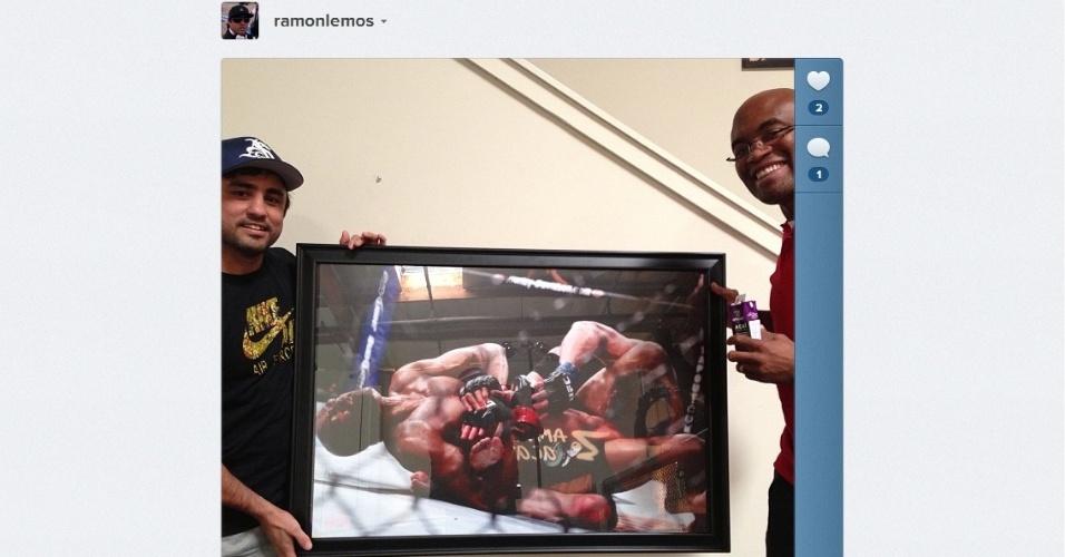 22.fev.2013 - Relembrando uma de suas lutas mais famosas, Anderson Silva posa com um quadro que mostra a finalização sobre Chael Sonnen no UFC 117, em 2010