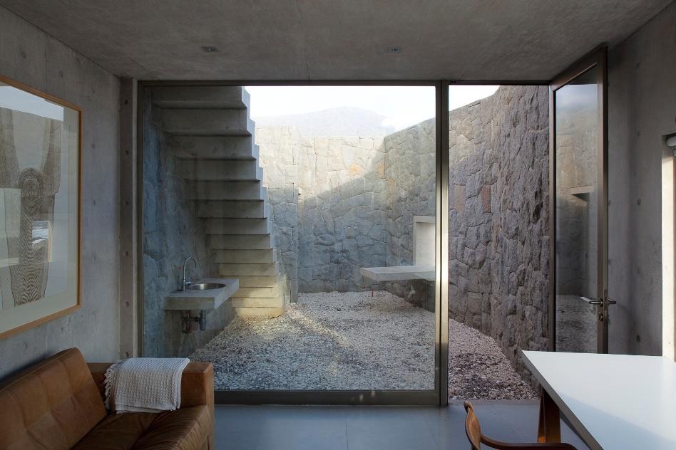 As paredes de pedra conferem um ar rústico à casa de formas predominantemente racionais. Na foto, um pequeno quintal anexo a uma das saletas das Casas del Horizonte, assinadas por Cristián Undurraga em Zapallar, Chile