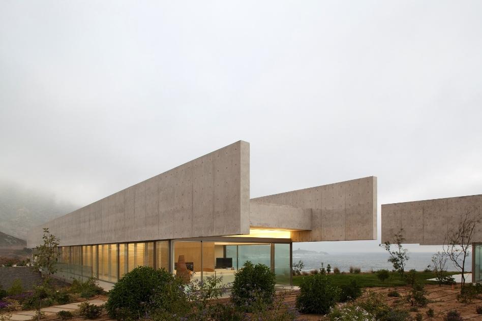 Estabelecendo um diálogo entre os volumes, as duas construções e suas grandes empenas de concreto compartilham um pátio e um jardim com plantas locais. O projeto das casas del Horizonte, no litoral chileno, é assinado pelo arquiteto Cristián Undurraga