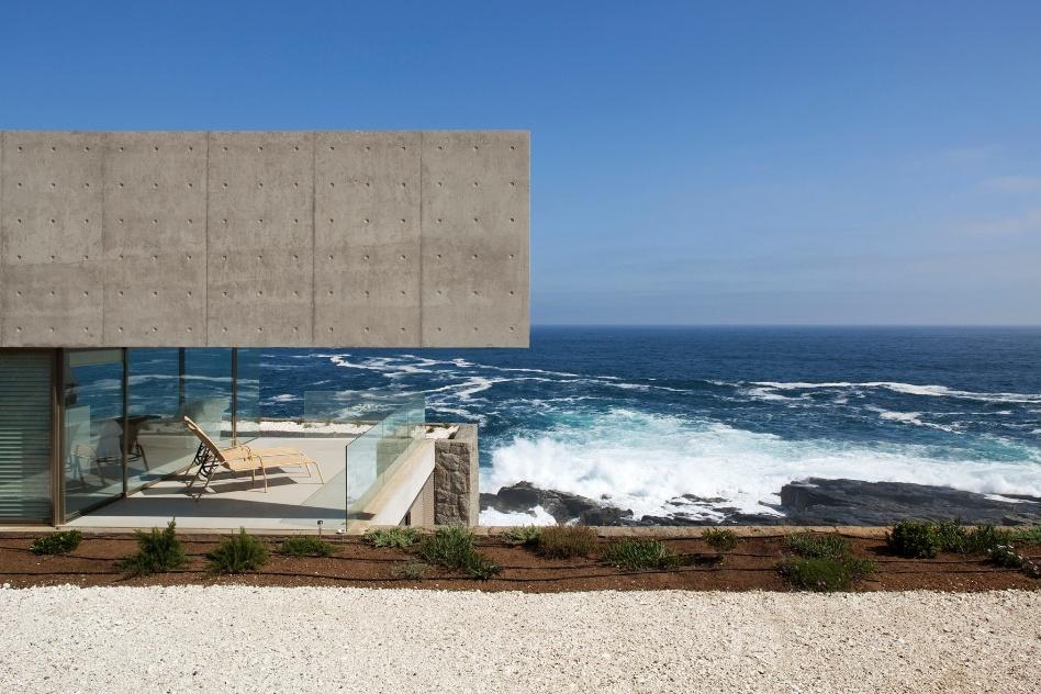 Na casa projetada por Cristián Undurraga no litoral chileno, a varanda no pavimento superior garante momentos de tranquilidade e contemplação para os usuários. As vigas de concreto sobre o bloco de vidro não escondem as marcas das fôrmas com as quais foram fabricadas