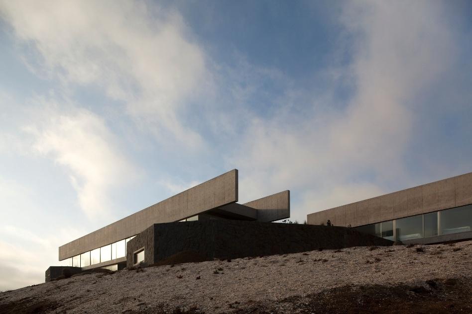 Os dois blocos horizontais com vistas panorâmicas parecem pousar no terreno rochoso e sobre os volumes de pedra. As construções ficam em Zapallar, balneário sofisticado na região central do Chile, e foram projetadas pelo arquiteto Cristián Undurraga