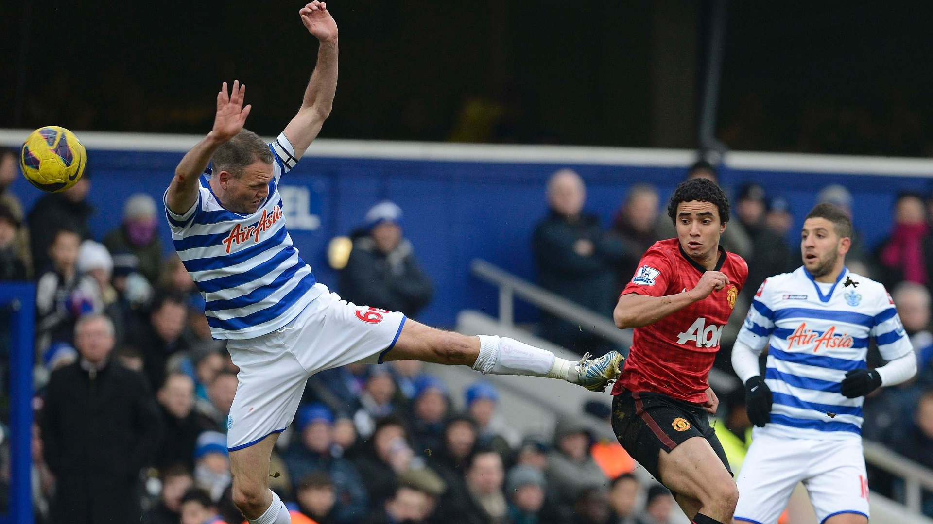 23.fev.2013 - Clint Hill (esq.), do Queens Park Rangers, dá voadora para tirar a bola do brasileiro Rafael (dir.), do Manchester United