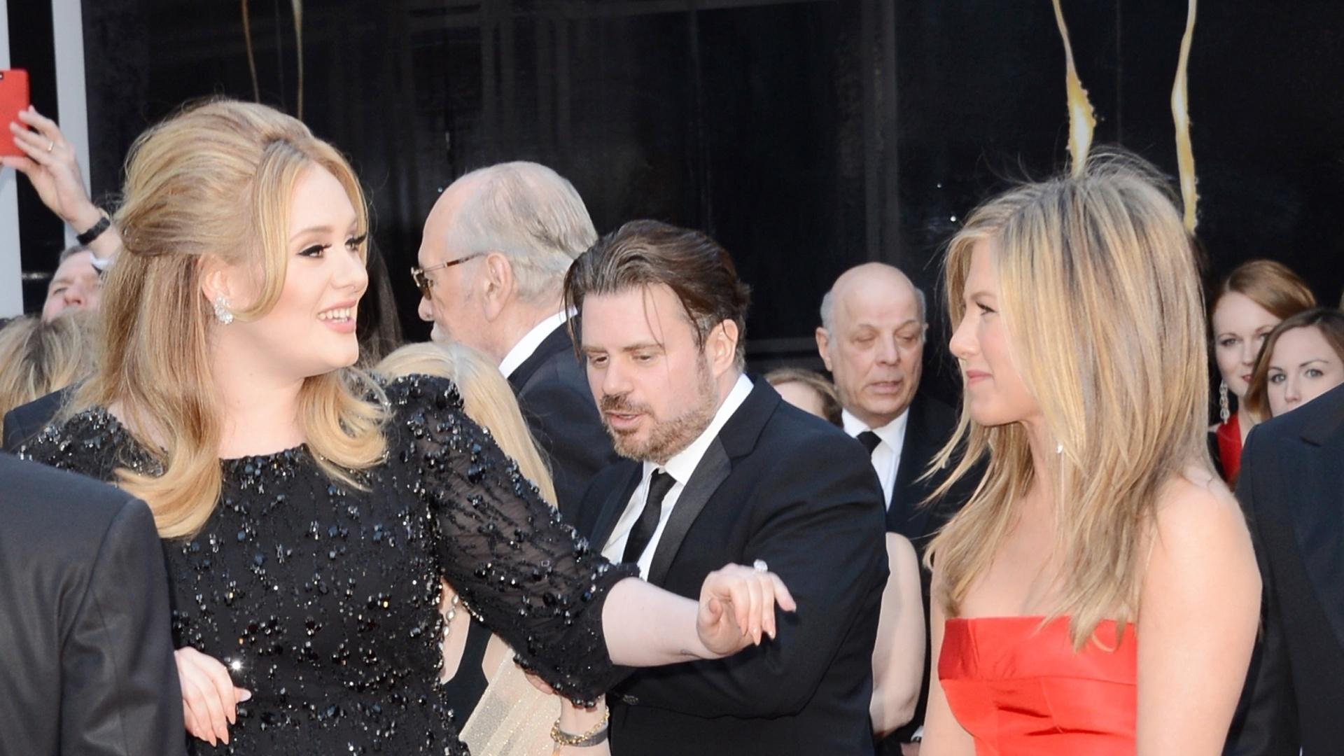 24.fev.2013 - A cantora britânica Adele acena para a atriz Jennifer Aniston no tapete vermelho do Oscar 2013