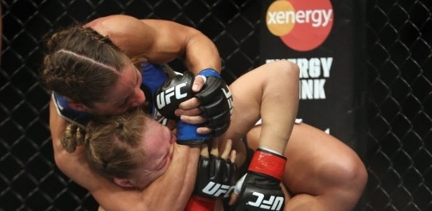 Liz Carmouche tenta pegar Ronda Rousey pelo pescoo durante luta vlida pelo UFC 157